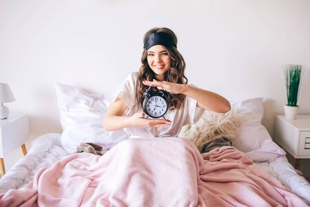 Dark haired beautiful young brunette wake up in her bed. Cheerful nice woman holding clock in hands and smile. Look straight on camera. Sleeping mask on forehead. Positive happy model in bedroom.