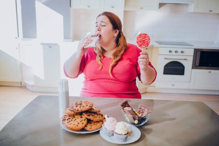 Fat young woman in kitchen sitting and eating sweet food. Biting chocolate. Cookies and cakes on table. Body positive. Daylight.