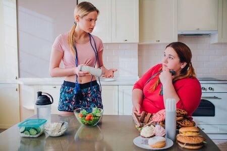 Young slim and overweight women look at each other in kitchen. Thin model hold bowl with salad in hands. Plus size woman sit and look at well-bilt model. Stock fotó