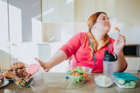 Fat young woman in kitchen sitting and eating healthy food. She show stop sign to sweet food and dont look at it. Plus size model hold for with tomato on it. Healthy food on right side. Stock fotó