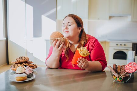 Fat young woman in kitchen sitting and eating junk food. Unhealthy lifestyle. Hold burger and french fries in hands. Body positive. Sweets on table. Daylight in kitchen.