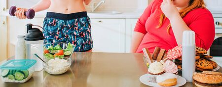 Cut view of young slim model and overweight woman in kitchen. Well-built girl hold dumbbells in hands. Fat woman look at her.