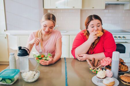 Young hungry slim and overweight women in kitchen eating food. Healthy and unhealthy meal. Salad vs burger. Body positive. Healthy lifestyle.