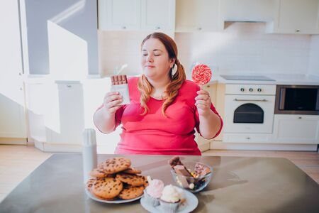 Fat young woman in kitchen sitting and eating sweet food. Cookies and cakes on table. Inside daylight. Body positive. 写真素材 - 128338639