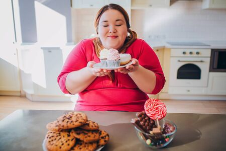 Fat young woman in kitchen sitting and eating sweet food. Plus size model hold small cakes in hands and look at them. Happy woman likes to eat. Body positive.