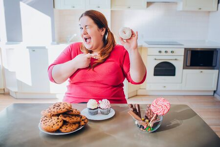 Fat young woman in kitchen sitting and eating sweet food. Happy plus size model smile on camera and point on donut. Daylight in kitchen. Cookies and pancakes on table. Body positive.