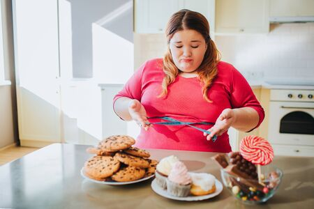 Fat young woman in kitchen sitting and eating sweet food. Confused serious plus size model look on sweets. Body positive. Soft tape measure around waist.