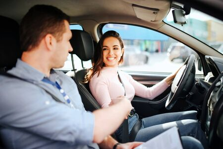 Male auto instructor takes exam in young woman. Brunette look at guy and smile. Driving car with confidence. Man point with hand.