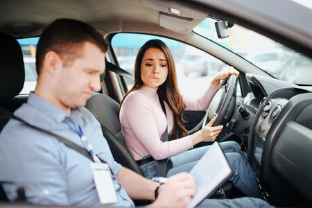 Male auto instructor takes exam in young woman. Worried young woman look at test results. Holding hands on steering wheel. Confused man look down. Daylight.