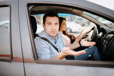 Male auto instructor takes exam in young woman. Wondered man look on camera. Confident female student driwing car and holding hands on steering wheel. Stock fotó