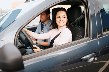 Male auto instructor takes exam in young woman. Cheerful positive and happy young woman driving car nd smile. Instructir sit besides and examine her.