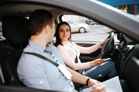 Male auto instructor takes exam in young woman. Calm peaceful confident female student look at teacher and smile. Hold hands on steering wheel and drive.
