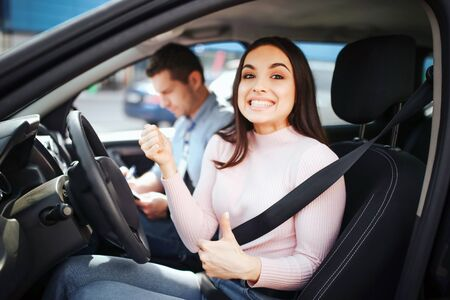 Male auto instructor takes exam in young woman. Happy positive model look on camera with big thumbs up. Smiling with likes. Instructor sit beside her. Passing exams. Daylight outside.