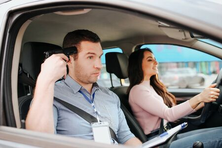 Male auto instructor takes exam in young woman. Tired crazy guy holding gun in hand and directing it to his head. Young female student driving car with fun.