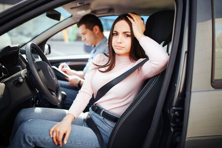Male auto instructor takes exam in young woman. Bored woman look on camera and pose. Sit together in car. Passed exam. Daylight. Stock fotó