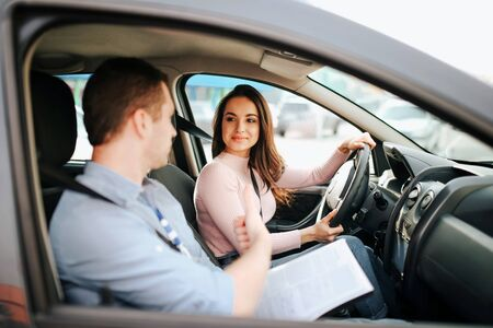 Male auto instructor takes exam in young woman. Positive happy model look at guy and smile. Driving car alone and careful. Guy talks to her. Passing exam.