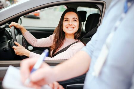 Male auto instructor takes exam in young woman. Cheerful attractive model look at guy and smile. Holding hands on steering wheel. Instructor writing mark on paper.