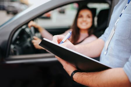 Male auto instructor takes exam in young woman. Blurred background of model sitting in car and holding hands on steering wheel. Guy hold folder with paper in hands.