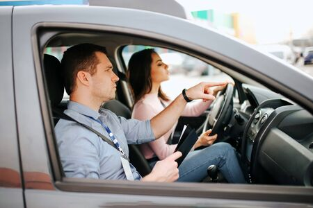 Male auto instructor takes exam in young woman. Careful driving and passing practical test. Instructor help with driving. Young woman pass test with confidence and very careful.