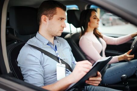 Male auto instructor takes exam in young woman. Careful serious look straight on road. Write on paper. Young woman careful driving. Concentrated. Passing practical test.