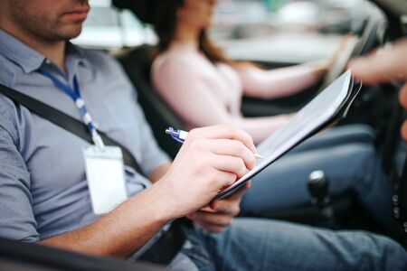 Male auto instructor takes exam in young woman. Close up of man writing on paper. Passing practical test. Young woman driving with confidence.