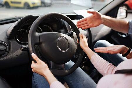 L'istruttore di auto maschio prende l'esame in giovane donna. Vista di taglio delle mani della donna sul volante. Guy indicalo e spiega. Siediti in macchina insieme. Ora dell'esame.
