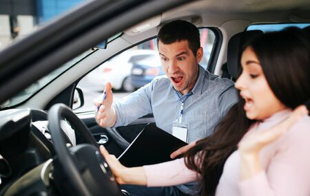 Male auto instructor takes exam in young woman. Screaming on brunette and point with hand. She look down and aegue. Stress and uncomfortable situation. Stock fotó
