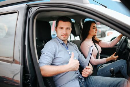 Male auto instructor takes exam in young woman. Happy positive young man look on camera and hold big thumb up. Careful young woman sriving car. Sit on drivers place and hold hands on steering wheel.