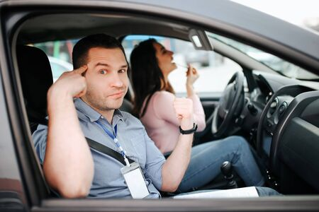Male auto instructor takes exam in young woman. Look on camera and point on head with finger. Mad student doing makeup in car. Look on mirror.