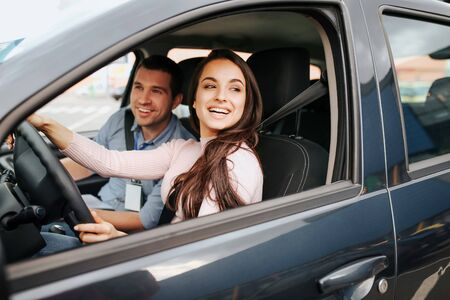 Male auto instructor takes exam in young woman. Cheerful attractive female driver posing at drivers place. Look from car. Hold hands on sheering wheel.