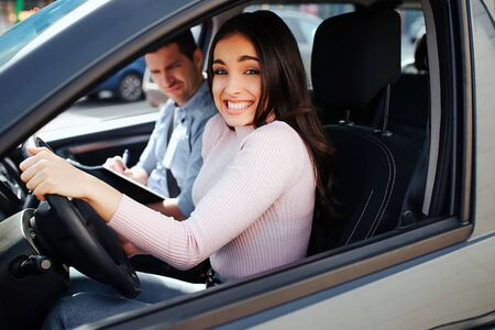 Male auto instructor takes exam in young woman. Confused stressed young woman drive car careless. Model look on camera. Unhappy young instructor sit besides.
