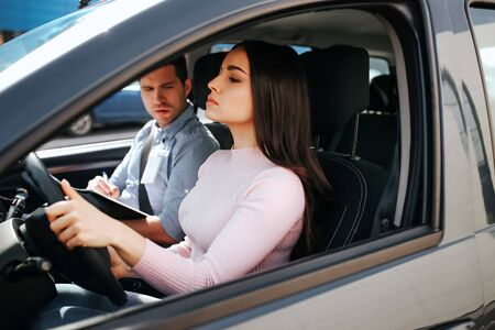 Male auto instructor takes exam in young woman. She hold hands on steering wheel and driving. Young man look at brunette with confusion. Model drives straight. Sit in car.