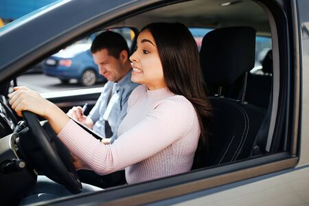 Male auto instructor takes exam in young woman. Brunette look confused straight on road and drive car. Hold hands on steering wheel. Instructor look down and write.