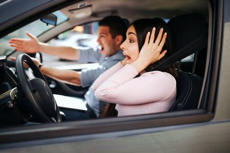 Male auto instructor takes exam in young woman. Screaming and yelling. Looking forward. Woman drive car but doesnt hold hands on steering wheel. Stress and discomfort. Stock fotó