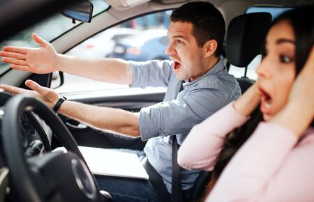 Male auto instructor takes exam in young woman. Stress during driving. Scared young woman touch head with hands. Instructor screaming and pointing forward. Stockfoto