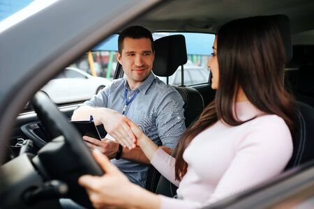 Male auto instructor takes exam in young woman. Shaking hands. Sitting in car. Brunette hold hand on steering wheel. Stock fotó