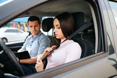 Male auto instructor takes exam in young woman. Brunette hold hands on seat belt and lock it. Young man sit besides with exam papers.
