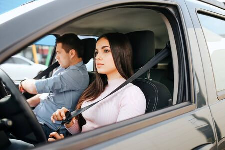 Male auto instructor takes exam in young woman. Serious brunette hold seat belt in hand and look straight. Guy prepare for driving. Stock fotó