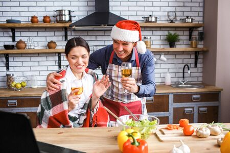 Cheerful happy man and woman in kitchen celebrating Christmas eve or new year. Look at laptop and wave with hands. Smile. Cooking in kitchen. Festive mood