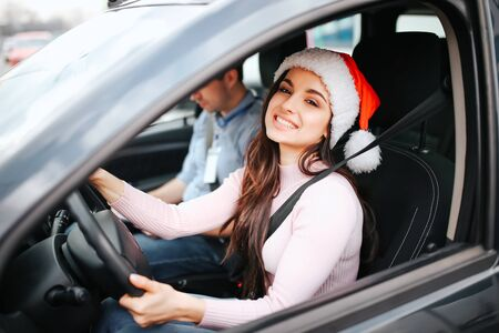 Picture of attractive young woman sit on drivers place. Hold hands on steering wheel and smile. Christmas or new year time. Wear red hat and smile. Man sit beside. Stock fotó