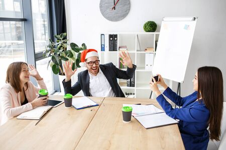 Workers in office. Celebrating new year or Christmas. People sit at table together. Brunette taking picture of man in red hat. Having fun at work.