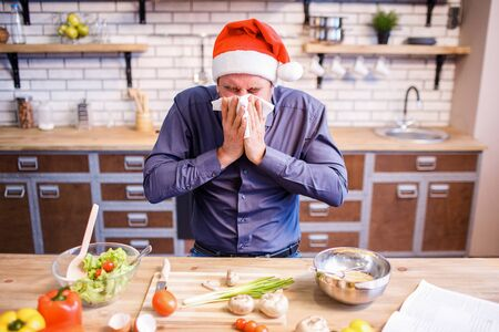 Sick ill man sit at table in kitchen. Cover nose with white tissue and sneeze. Celebrating new year of Christmas. Alone. Vegetables on table Stock fotó