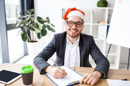 Young cheerful businessman in office. Celebrating new year or Christmas. Working alone. Writing notes. Festive mood. Positive cheerful nice man.