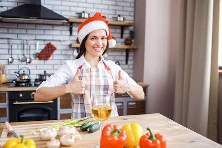 Festive attractive adult woman hold both big thumbs up and smile. Celebrating new year or Christmas. Cooking alone. Daylight. Looking on camera.