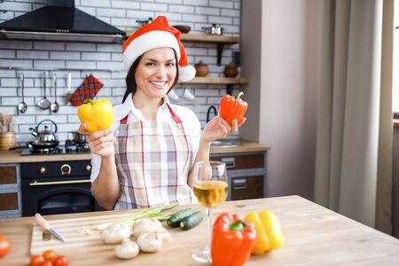 Cheerful adult woman stand in kitchen and posing on camera. Red hat on head. Hold colorful peppers in hands. Cooking and celebrating new year or Christmas. Stock fotó