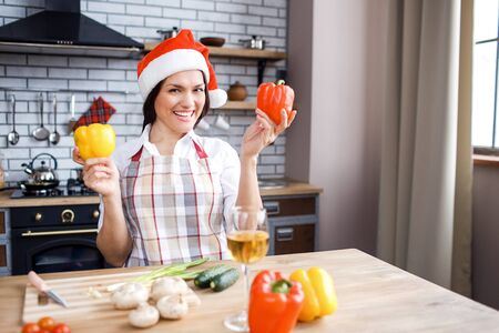 Adult attractive woman stand in kitchen and posing on camera. Holding peppers in hands. Wear red festive hat. Celebrating Christmas or new year. Cooking alone.