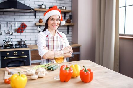 Positive happy adult woman posing on camera in kitchen. Wear festive red hat. Hands crossed. Celebrate new year or Christmas. Cooking alone. Stock fotó