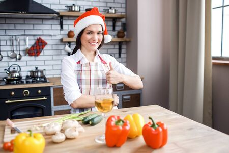 Beautiful attractive woman in red hat stand in kitchen and pose on camera. Celebrating Christmas and new year. Holding big thumb up and smile. Cooking. Festive mood. Stock fotó