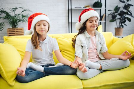 Young calm and peaceful teenagers meditating