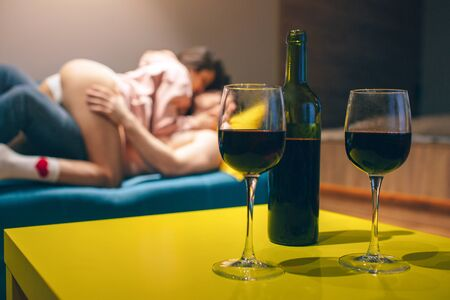 Young couple have in kitchen in night. Seductive sensual people in position on sofa. Wine bottle stand on table with glasses.